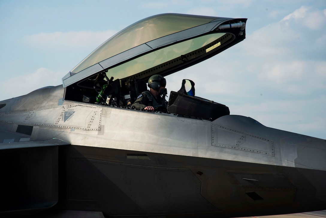 A pilot of an F-22 Raptor poses for a photo Nov. 6, 2019, at Tyndall Air Force Base, Florida. The pilot, airframe, and maintenance team supported Checkered Flag 20-1, which is a large-scale aerial exercise designed to integrate fourth and fifth-generation airframes to enhance mobility, deployment, and employment capabilities of aviators and maintainers. The exercise involved airpower assets, more than 50 aircraft, and support personnel from multiple installations. Aircraft and pilots participated in a Weapons System Evaluation Program and are evaluated on air-to-air and air-to-ground operations, providing a unique training environment. (U.S. Air Force photo by Staff Sgt. Magen M. Reeves)