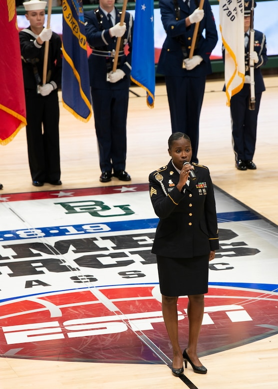 U.S. Army Sgt. Ashia Hunter, 9th Army Band vocalist, sings the national anthem during the ninth annual Armed Forces Classic at the Alaska Airlines Center in Anchorage, Alaska, Nov. 8, 2019. ESPN hosted the event in partnership with Joint Base Elmendorf-Richardson, Alaska. Every year, the Armed Forces Classic travels to a new military location around the world. The Marine Corps will host the 2020 Armed Forces Classic at Camp Lejeune, North Carolina.