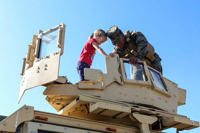 A Marine and a child stand atop a military vehicle and peer inside.