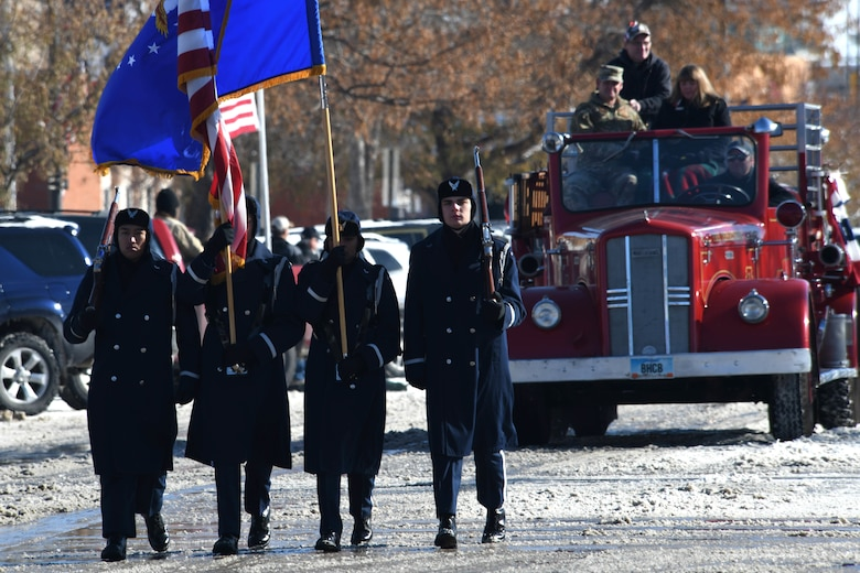 The Ellsworth Air Force Base, S.D., Honor Guard walks in the 2019 Veteran's Day Parade ahead of the flagship fire truck on Main Street in Rapid City, S.D., Nov. 11, 2019. Col. David A. Doss, 28th Bomb Wing commander, and his spouse, Marlina, rode in the truck and waved to those in attendance. (U.S. Air Force photo by Staff Sgt. Hailey Staker)