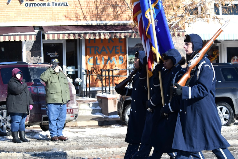 A veteran salutes the flag as the Ellsworth Air Force Base, S.D., Honor Guard walks in the 2019 Veteran's Day Parade on Main Street in Rapid City, S.D., Nov. 11, 2019. The Veteran's Day Ceremony and Parade celebrate and honor the nation's veterans, and included a flag ceremony by the Honor Guard. (U.S. Air Force photo by Staff Sgt. Hailey Staker)