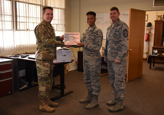 U.S. Air Force Airman 1st Class William Stokes, center, 60th Communications Squadron knowledge management technician, is recognized by Col. Jeffrey Nelson, left, 60th Air Mobility Wing commander, and Chief Master Sgt. Derek Crowder, right, 60th AMW command chief, as Warrior of the Week Nov. 12, 2019, at Travis Air Force Base, California. Stokes was recognized as the WoW for Nov. 10-16. The program highlights a Travis Airman for his or her outstanding performance. (U.S. Air Force photo by Airman 1st Class Cameron Otte)