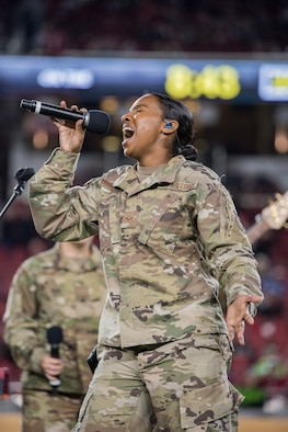 U.S. Airman sings into a microphone during an NFL halftime show