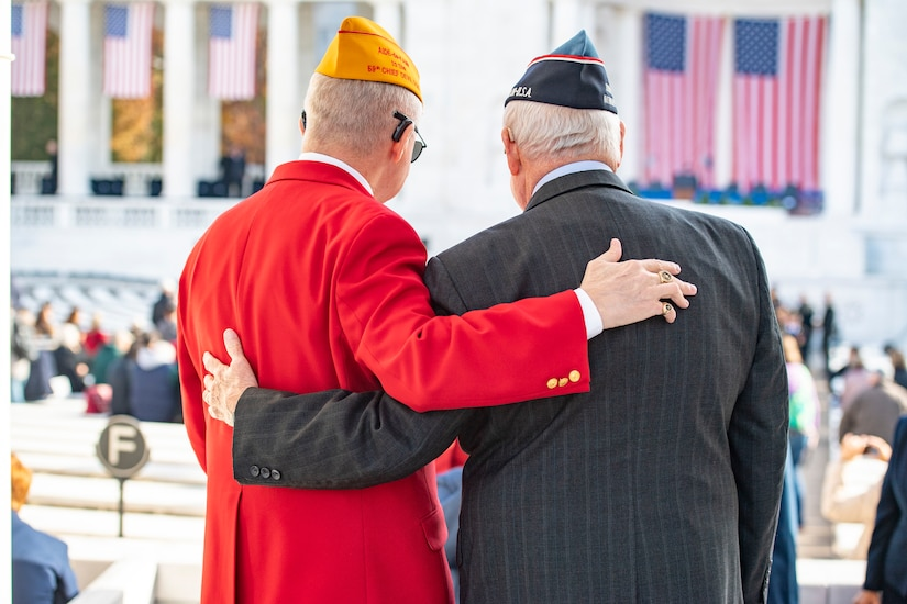 Two veterans, shown from behind, stand with their arms around each other at an amphitheater.
