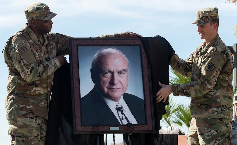 Col. Alfred Flowers, 99th Medical Group commander, and U.S. Army Staff Sgt. Brian O'Callaghan reveal a portrait of O'Callaghan during a ceremony celebrating the Mike O'Callaghan Military Medical Center's 25th Anniversary on Nellis Air Force Base, Nevada, Nov. 12, 2019. The portrait will hang in the MOMMC to honor the centers namesake. (U.S. Air Force photo by Senior Airman Kevin Tanenbaum)