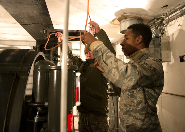 U.S. Air Force Airman 1st Class Marquis Brown, 786th Civil Engineer Squadron power production technician, works with Lithuania air force Pvt. 3rd Class Aurimas Kantauskas, aircraft arresting system technician, on an aircraft arresting system engine at Ramstein Air Base, Germany, Nov. 7, 2019. The aircraft arresting system is a mechanism designed to stop airplanes in the event pilots cannot stop them on their own.