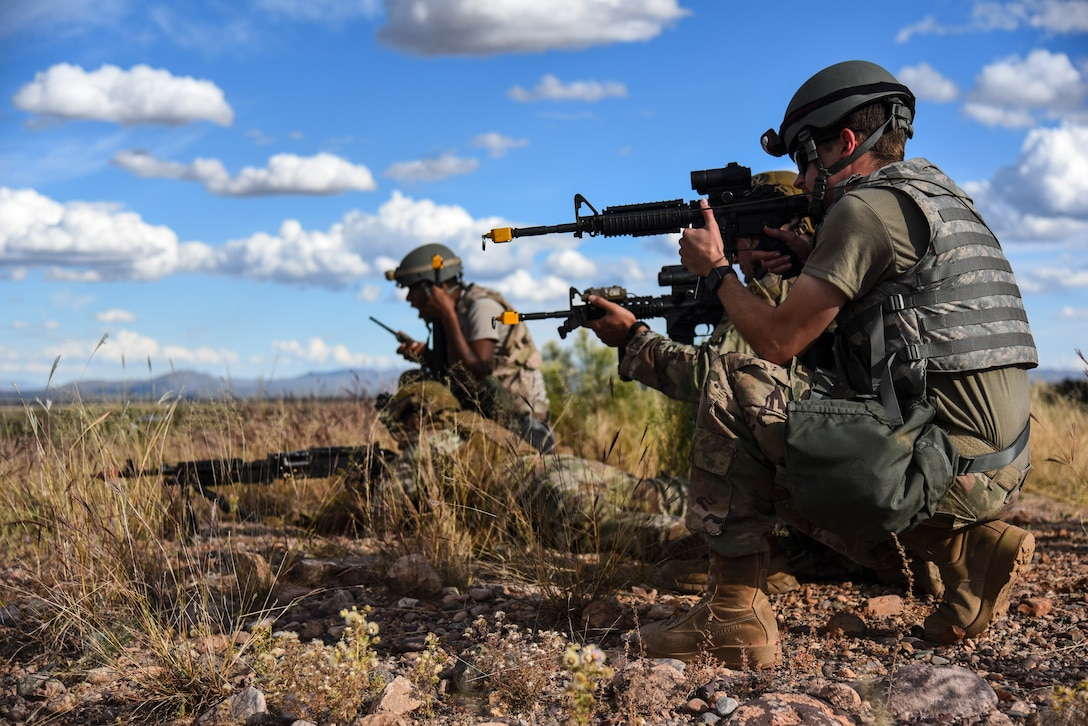 Troops with guns crouch in a desert.