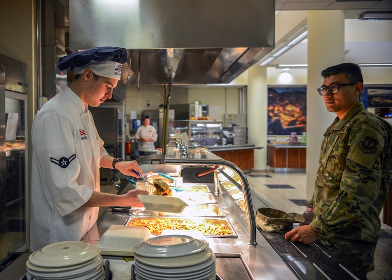 U.S. Airman Kellan S. Hill, 31st Force Support Squadron server, serves an Airman at La Dolce Vita dining facility, Aviano Air Base, Italy, Nov. 7, 2019. Hill joined the military May 7, 2019 and has worked at La Dolce Vita for one month. (U.S. Air Force photo by Airman Thomas S. Keisler IV)