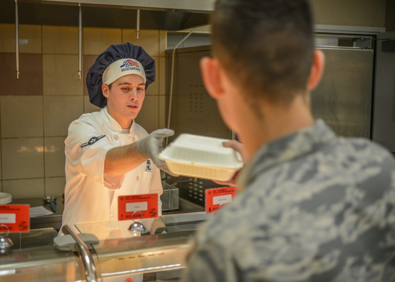 U.S. Airman Kellan S. Hill, 31st Force Support Squadron server, hands an Airman their order at the La Dolce Vita dining facility, Aviano Air Base, Italy, Nov. 7, 2019. La Dolce Vita offers numerous specialty meals to include Airman Appreciation meals, Mongolian, and Pancake Extravaganzas, as well as celebrating all national holidays including Thanksgiving and Christmas. (U.S. Air Force photo by Airman Thomas S. Keisler IV)