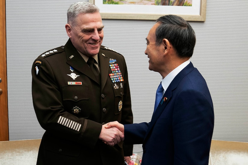 General and man in civilian suit shake hands.
