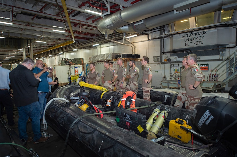 Civilian Journalists discuss divers' roles in Mine Counter Measures (MCM) during the International Maritime Exercise 2019 (IMX 19), with the French navy divers. The exercise is a multinational engagement involving partners and allies from around the world designed to facilitate the sharing of knowledge and experiences across the full spectrum of defensive maritime operations. IMX 19 serves to demonstrate the global resolve in maintaining regional security and stability, freedom of navigation and the free flow of commerce from the Suez Canal south to the Bab el-Mandeb Strait through the Strait of Hormuz to the Northern Arabian Gulf. (U.S. Navy photo by Mass Communication Specialist 3rd Class Darienne Slack