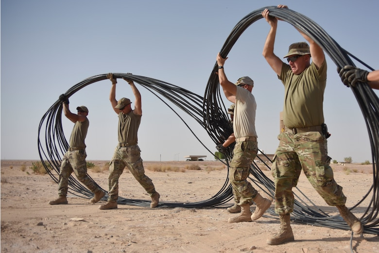 Airmen with the 210th Engineering Installation Squadron move fiber optic cable into place prior to running it to the next access point at Prince Sultan Air Base, Saudi Arabia on Nov. 5, 2019.