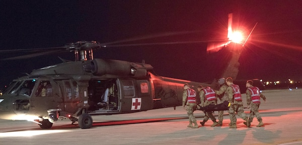 Soldiers load a simulated casualty onto a waiting UH-60 Black Hawk helicopter at Joint Base San Antonio-Kelly Airfield as part of a U.S. Army Forces Command Emergency Deployment Readiness Exercise Nov. 4, 2019. The exercise tested Brooke Army Medical Center staff's ability to receive and provide definitive care to wartime trauma victims, as part of its Role IV wartime mission.
