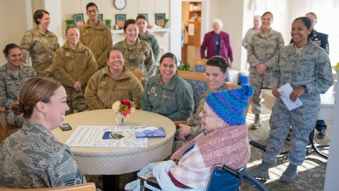 Airmen visit with Della Sassa around a table in a function room at the Royal Cape Cod Nursing and Rehabilitation Center