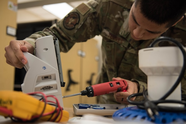 U.S. Air Force Airman 1st Class Timothy Torres, 633rd Medical Group biomedical equipment technician, unscrews a panel on a vital signs monitor at Joint Base Langley-Eustis, Virginia, Nov. 8, 2019. Torres removed the panel so the motor could be repaired. (U.S. Air Force photo by Airman 1st Class Sarah Dowe)