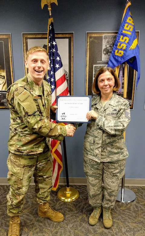Master Sgt. Angela Hayden, 14th Intelligence Squadron first sergeant, presents the September 2019 Diamond Sharp Award to Senior Airman Robert Stephens, 14th IS Intelligence analyst, Nov. 6, 2019. The award is for exemplary performance, adherence to the Air Force Core Values, attitude, appearance and ability. (Courtesy photo)