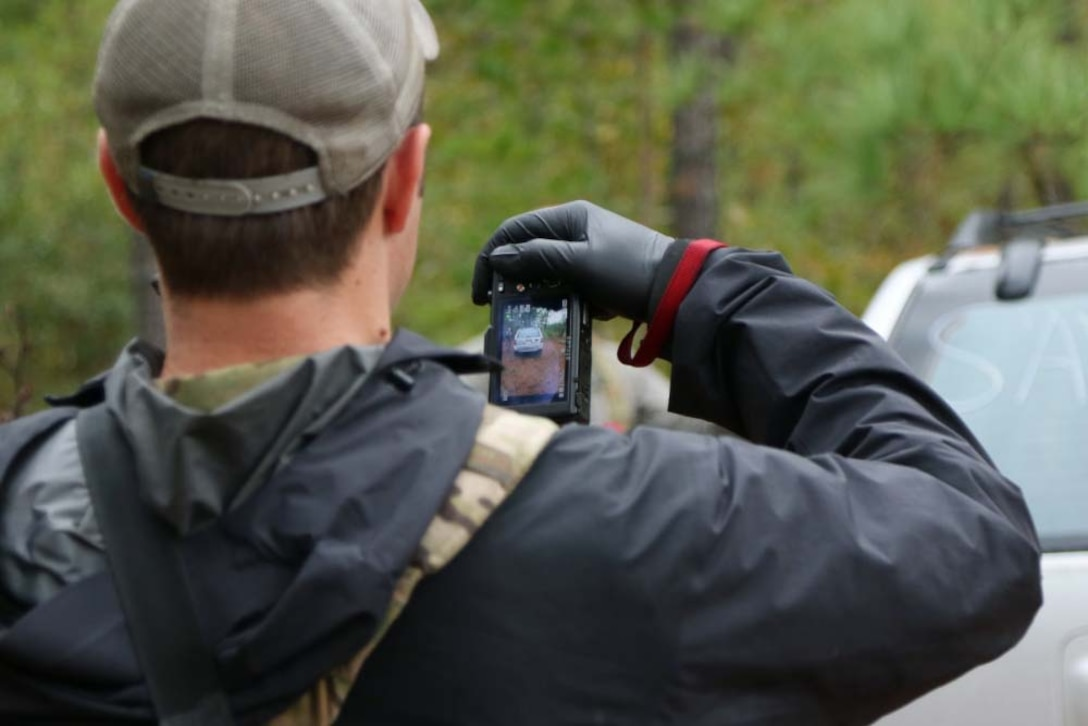 Photo of a man from the back; he is holding a device with a small screen in one hand.
