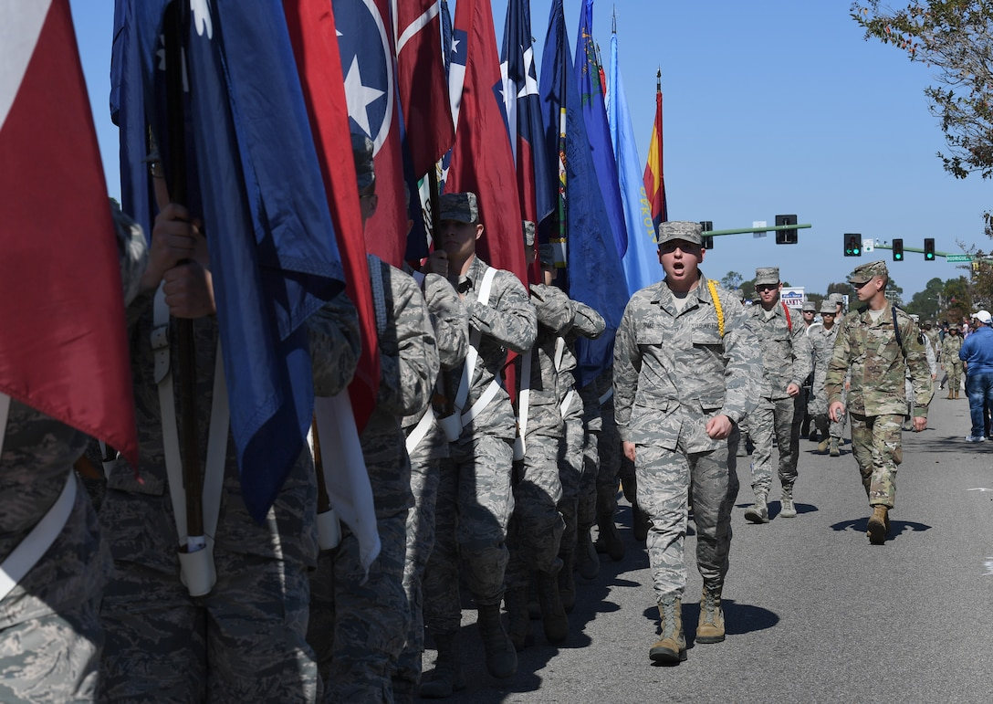 Airmen from the 81st Training Group carrying the 50 state flags march in the 19th Annual Gulf Coast Veterans Day Parade in DíIberville, Mississippi, Nov. 9, 2019. Keesler Air Force Base leadership, along with hundreds of Airmen, attended and participated in the parade in support of all veterans past and present. More than 70 unique floats, marching bands and military units marched in the largest Veterans Day parade on the Gulf Coast. (U.S. Air Force photo by Kemberly Groue)