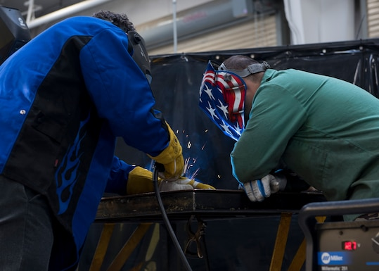 U.S. Air Force Airman and a city representative weld sheet metal together, November 7, 2019, on Mountain Home Air Force Base, Idaho. Civic leaders were able to weld sheet metal and use a sand cutter to cut out shapes of Idaho. (U.S. Air Force photo by Airman Natalie Rubenak)