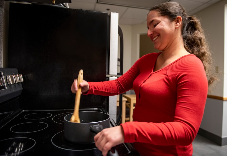 Airman 1st Class Katie Naquin, 50th Force Support Squadron customer service journeyman, cooks in the Layne Hall dayroom at Peterson Air Force Base, Colorado, Nov. 12, 2019. Naquin plans to cook stuffing for a meal with friends this Thanksgiving. (U.S. Air Force photo by Airman Amanda Lovelace)