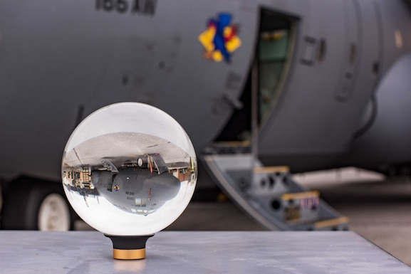 A C130H2 receiving maintenance is viewed through a photographic lens ball at New Castle Air National Guard Base, Del., Oct. 29, 2019. The 166th Aircraft Maintenance Squadron is testing the Conditions Based Maintenance program, which uses predictive analytics to proactively schedule aircraft maintenance. (U.S. Air National Guard photo by Mr. Mitch Topal)
