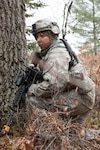 Master Sgt. Tammy Marks, 167th Secuirty Forces Squadron, kneels in a wooded area during a comabt training scenario, Nov. 5, 2019. Approximately 300 members of the 167th Airlift Wing, Martinsburg, W.Va., deployed to the Combat Readiness Training Center in Alpena, Mich., Nov. 3-7, for a full-scale readiness exercise.