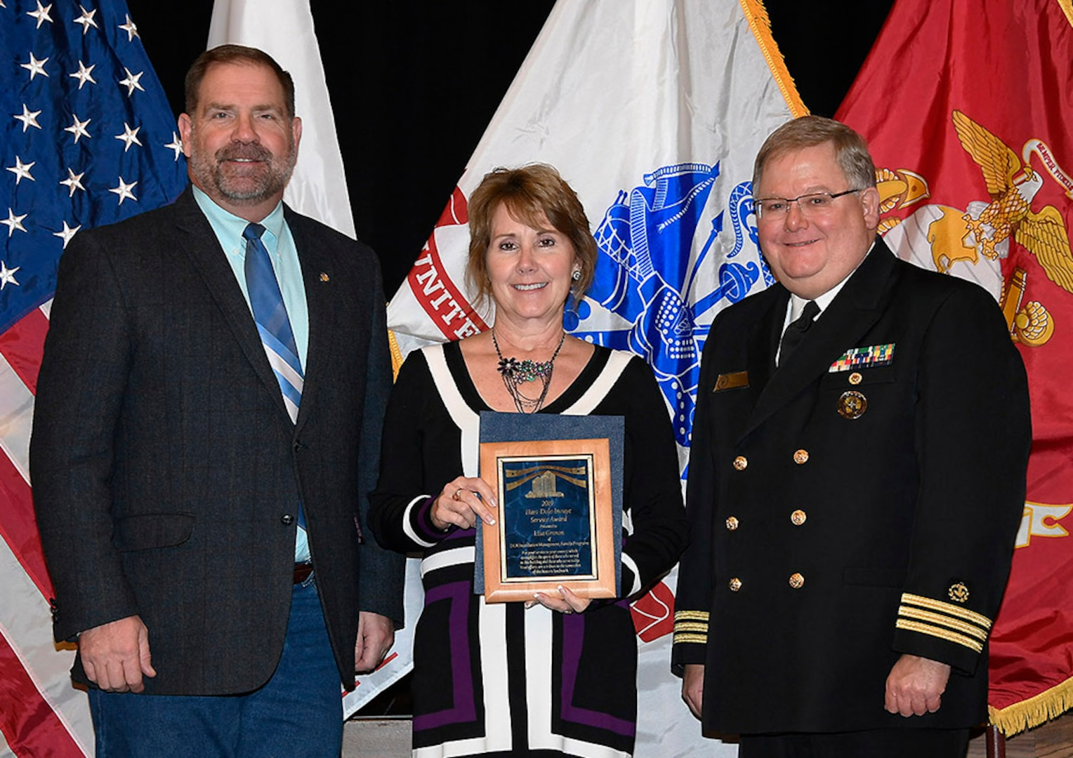 DLA Installation Management's Lisa Grenon (center) is awarded a 2019 Hart-Dole-Inouye Federal Center Service Award Nov. 8. Also pictured are DLA Disposition Services Director Mike Cannon and Battle Creek Military Affairs Committee Chairman T.R. Shaw, U.S. Navy, retired.
