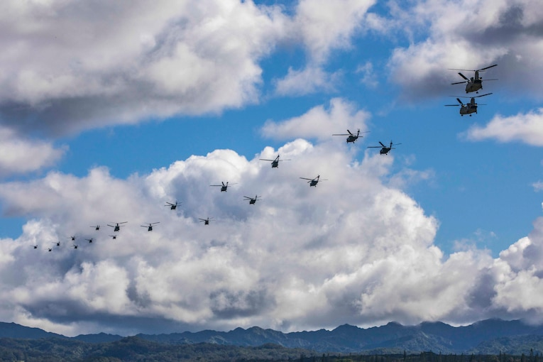 A large group of helicopters travel through the sky.