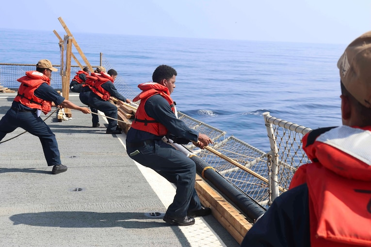 A group of sailors pull on rope on a ship's deck.