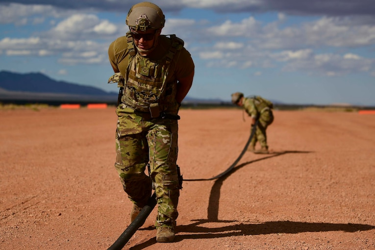 Two airmen pull a hose in opposite directions.