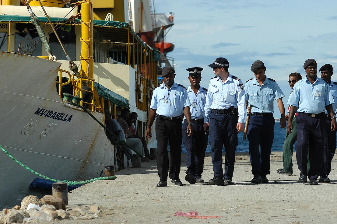 Regional Assistance Mission to Solomon Islands (RAMSI) and Royal Solomon Islands Police patrol Honiara waterfront. Solomon Islands, 2003. Following years of unrest in the Solomon Islands, a sizable international security contingent of more than 2,000 police and troops, led by Australia and New Zealand and with representatives from six other PICs arrived in summer 2003 to help restore security. RAMSI, as the force was known, ended its mission in 2017. Photo by Brian Hartigan, Australian Federal Police