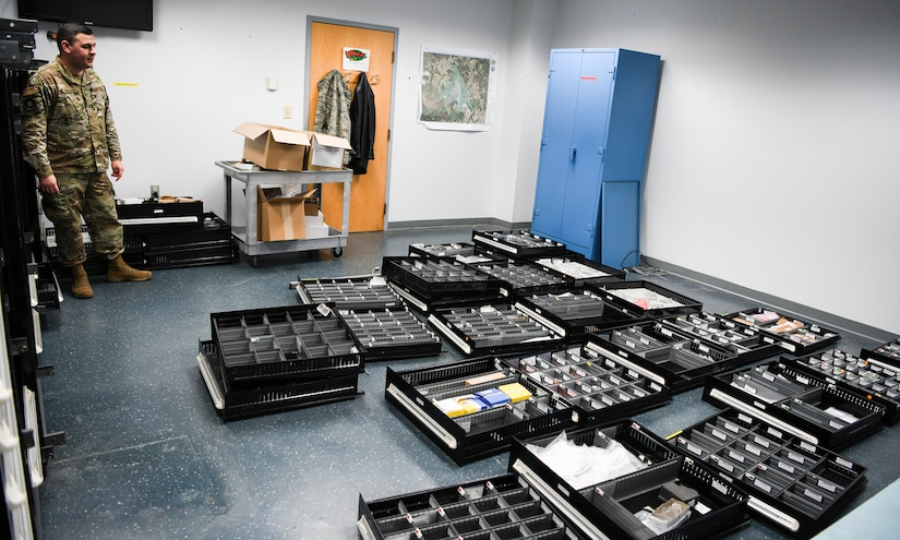 U.S. Air Force Staff Sgt. Slade Muraira, 437th Aircraft Maintenance Squadron shift leader, stands with the older tool boxes and containers that previously held the Tool Room's extensive inventory of parts at Joint Base Charleston, S.C., Nov. 8, 2019. The new auto-mated tool crib will be able to hold the same amount of tools and maintenance parts and only take up half the space. The Airmen and NCOs of the support tool room went through a yearlong process of requesting and justifying the purchase of an automated tool crib to not only improve the quality of life for their Airmen in the shop, but also to increase their shop's positive impact on the Joint Base Charleston flightline. The tool crib will save over 1000 man hours in labor by automatically keeping accountability of any of the tools and parts that are checked out as well as assisting in keeping a constant inventory on items in stock. The machine will also notify members when new parts should be ordered based on the supply and demand tempo of each individual part.