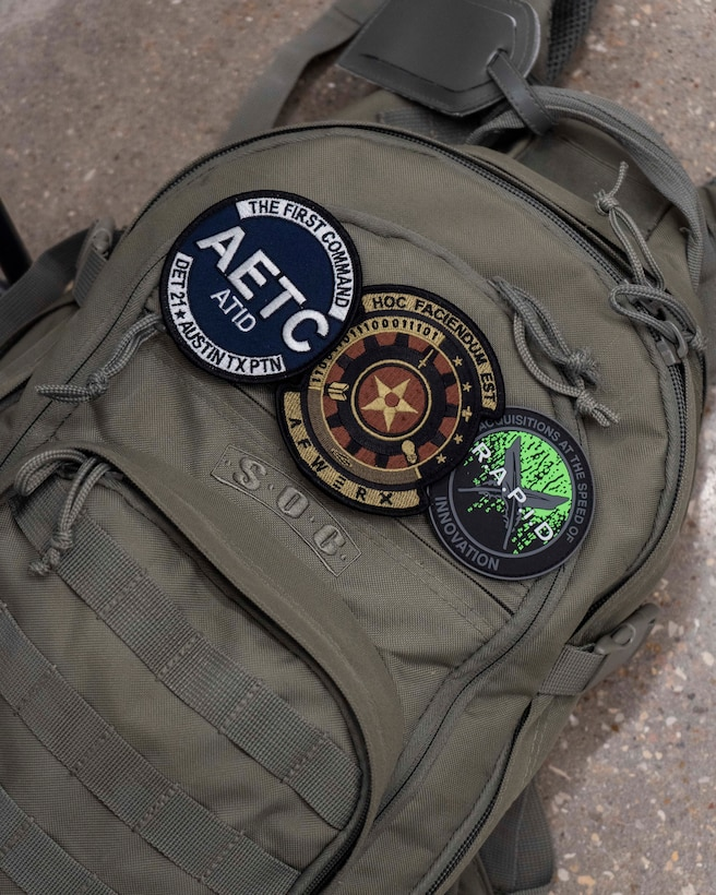 Three patches stick to Lt. Col. Jorge Manresa's backpack at the AFWERX-Austin hub, Texas, Nov. 5, 2019. Similar to most people who work in the defense innovation space, Manresa has played many roles as part of organizations like the Air Force Installation Contracting Center, Air Education and Training Command Technology Integration Detachment, and AFWERX. Projects taken on by various Air Force units like Project NEXUS and Pilot Training Next are bolstered by collaboration between different career fields, ranks, and missions. (Air National Guard Photo by Staff Sgt. Jordyn Fetter)
