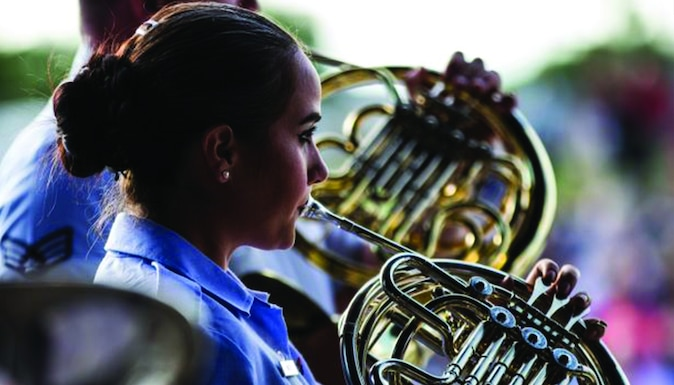 An Academy Band French horn player performs in her blue uniform during a 2019 concert band Independence Day tour.