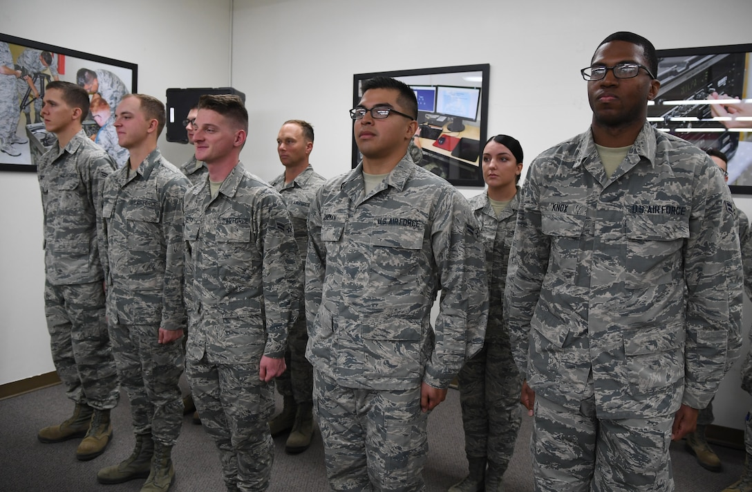 Airmen stand in formation during the 338th Training Squadron radio frequency transmission systems course graduation inside Jones Hall at Keesler Air Force Base, Mississippi, Nov. 8, 2019. Phil Bryant, Governor of Mississippi, presented certificates to the nine course graduates during the ceremony. (U.S. Air Force photo by Kemberly Groue)