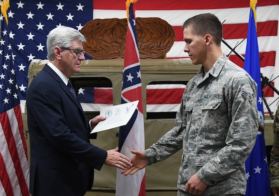 Phil Bryant, Governor of Mississippi, presents a graduation certificate to U.S. Air Force Airman 1st Class Weston Aces, 338th Training Squadron student, during the radio frequency transmission systems course graduation inside Jones Hall at Keesler Air Force Base, Mississippi, Nov. 8, 2019. Bryant presented certificates to the nine course graduates during the ceremony. (U.S. Air Force photo by Kemberly Groue)