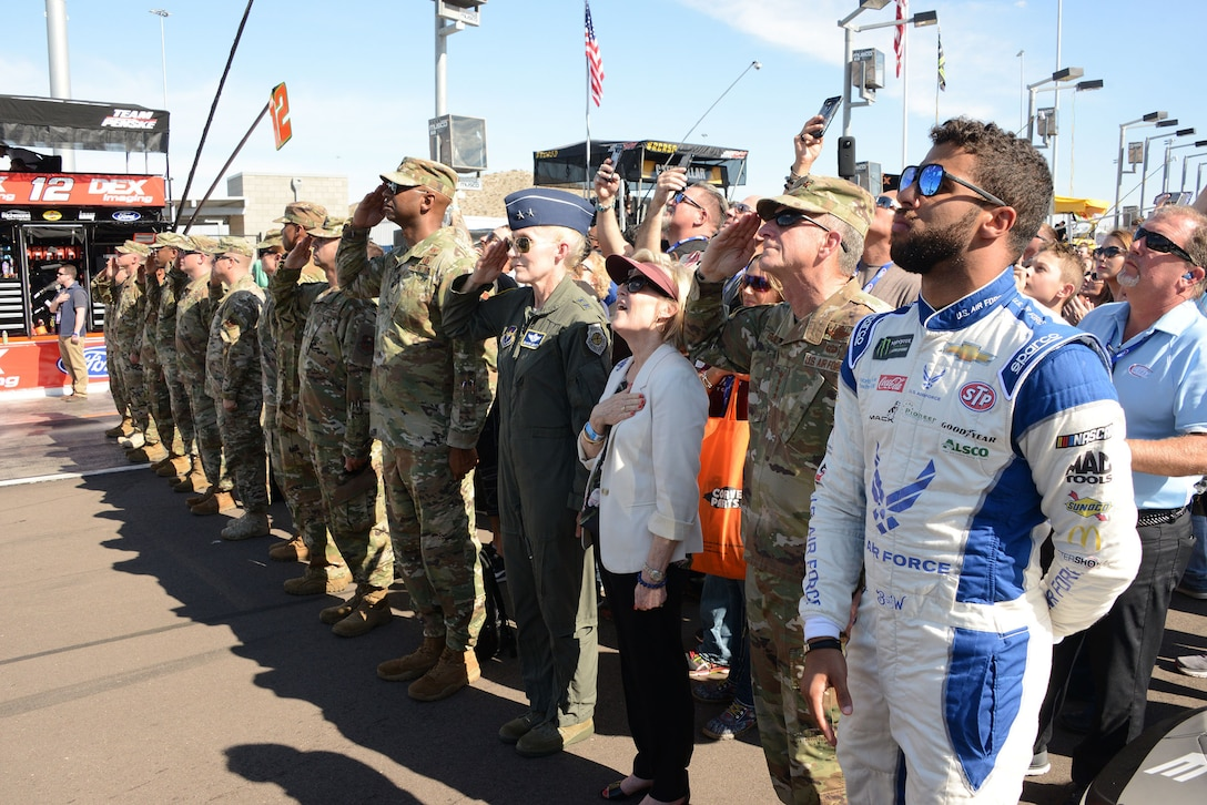 Bubba Wallace, driver of the Air Force No. 43 car, Gen. David. L. Goldfein, the Air Force chief of staff,  and his wife Dawn Goldfien, Maj. Gen. Jeannie Leavitt, Air Force Recruiting Service, commander, and members of the Air Force during the national anthem before the the Bluegreen Vacations 500 NASCAR race in Phoenix.