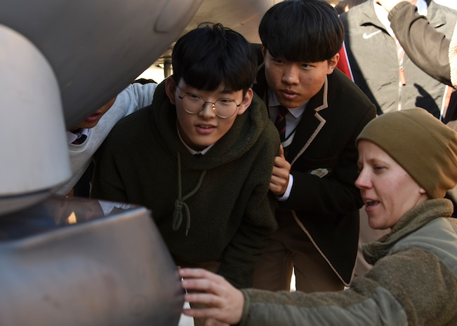 U.S. Air Force Tech. Sgt. Sarah Allen, 35th Aircraft Maintenance Unit electric and environmental craftsman, tells students from Gunsan Dong High School about the capabilities of the F-16 Fighting Falcon during a tour at Kunsan Air Base, Republic of Korea, Nov. 8, 2019. This was the first time the students were able to visit Kunsan and get up close and personal with an F-16. (U.S. Air Force photo by Staff Sgt. Anthony Hetlage)