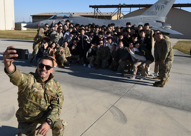 U.S. Air Force Staff Sgt. John Lace, 8th Aircraft Maintenance Squadron dedicated crew chief, takes a selfie with a group of students from Gunsan Dong High School at Kunsan Air Base, Republic of Korea, Nov. 8, 2019. Lace spoke to the students about the capabilities of the F-16 Fighting Falcon including its cost, payload and his role in the repair of the aircraft. (U.S. Air Force photo by Staff Sgt. Anthony Hetlage)