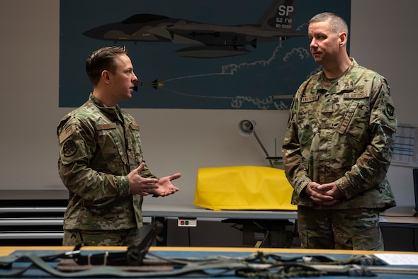 U.S. Air Force Staff. Sgt. Jacob Wade, 52nd Operations Support Squadron aircrew flight equipment craftsman, left, speaks with Chief Master Sgt. Randy Kwiatkowski, Third Air Force command chief, right, at Spangdahlem Air Base, Germany, Nov. 13, 2019. Kwiatkowski visited various locations around Spangdahlem AB to get to know Airmen. Wade briefed Kwiatkowski on the importance of attention to detail when packing a parachute. (U.S. Air Force photo by Airman 1st Class Valerie Seelye)