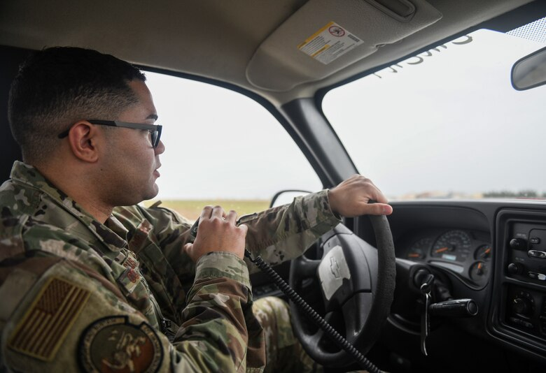U.S. Air Force Staff Sgt. Deuderit Colon De Jesus, an airfield management operations supervisor from the 31st Operations Support Squadron, uses a radio to request permission from the air traffic control tower to cross the runway at Aviano Air Base, Italy, Nov. 13, 2019. The 31st Operations Support Squadron develops wing war plans, administers weapons and tactics programs and provides current operations planning, air traffic control, airfield management, weather and intelligence support. (U.S. Air Force photo by Airman 1st Class Ericka A. Woolever).