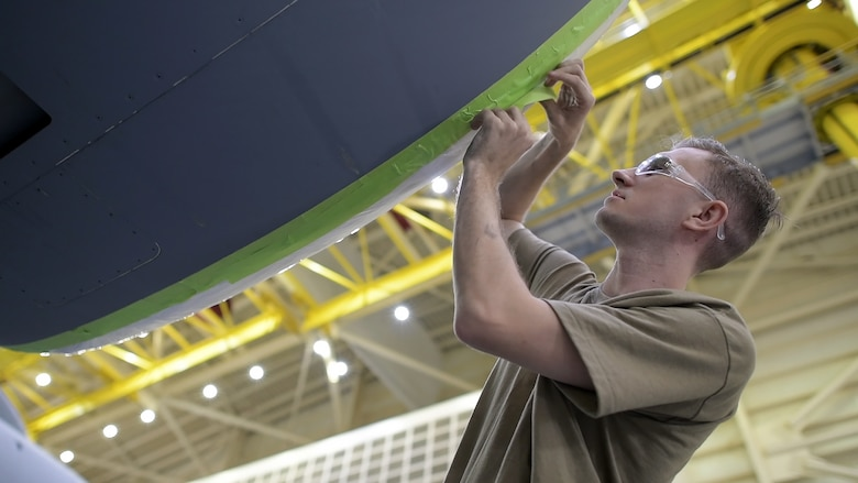 Senior Airman Ian Roush, 437th Maintenance Squadron, Fabrication Flight corrosion control and structural repair, pre-masks a C-17 engine prior to sanding the Aircraft Oct. 15, 2019, at Joint Base Charleston, S.C. Pre-masking is the first step prior to painting the aircraft. Approximately 12 aircraft go through the corrosion control process annually and it takes approximately two weeks complete each C-17.