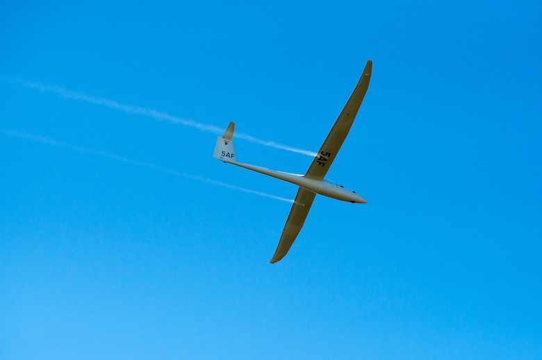 An Air Force Academy cadet piloting a glider performs during the Parents' Weekend Parade, Aug. 22, 2019, at the U.S. Air Force Academy, Colo. The Academy's aerobatics team uses the TG-16A Glider, a two-seat, engine-less glider. The glider is towed to a designated altitude by a Piper Super Cub tow plane before being released and soaring in-flight by using thermals and prevailing winds. (U.S. Air Force photo/Trevor Cokley)