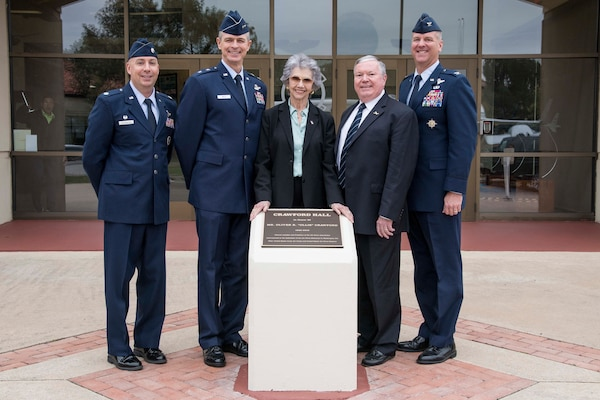 """(From left to right) U.S. Air Force Lt. Col. Eric Bissonette, 558th Flying Training Squadron commander; Maj. Gen. Craig Wills, 19th Air Force commander; Nancy Crawford, wife of the late Oliver """"Ollie"""" Crawford, James Clark, family friend of the Crawford family; and Col. Mark Robinson, 12th Flying Training Wing commander, stand in front of the dedication naming the 558th Flying Training Squadron building Crawford Hall. The dedication ceremony was held Nov. 13, 2019, at Joint Base San Antonio-Randolph, Texas, and is home to the sole source for all U.S. Air Force and U.S. Marine Corps undergraduate remotely piloted aircraft pilot and sensor operator training. Crawford was a pilot, charter member of the Air Force Association and was instrumental in the formation of the Air Force Memorial in Washington, D.C. (U.S. Air Force photo by Sean M. Worrell)"""