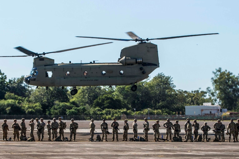 A group of soldiers stand underneath a helicopter.