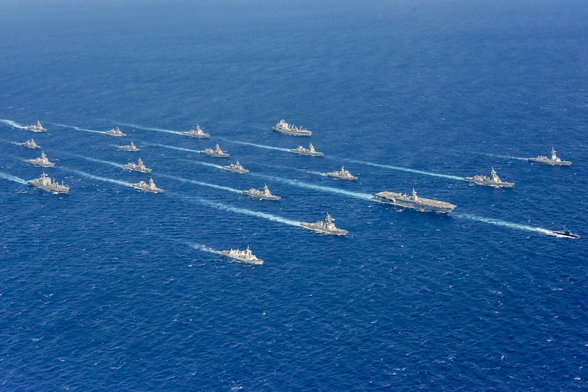 A large group of ships sail in formation.