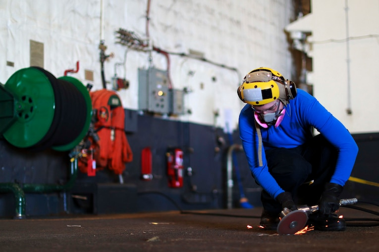 A sailor kneels on the ground using a saw on a pad eye.