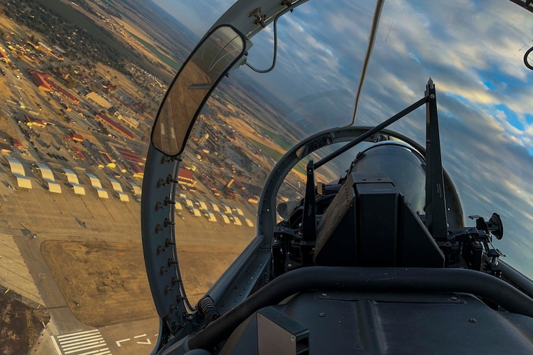 An airman sits in a cockpit while flying over a city.