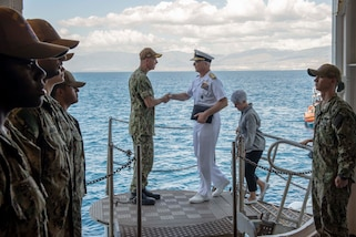 U.S. Navy Capt. Charles Cather, left, assigned to the hospital ship USNS Comfort (T-AH 20), welcomes Adm. Craig S. Faller, commander, U.S. Southern Command, to the ship while it is anchored off the coast of Port-Au-Prince, Haiti, Nov. 7, 2019.