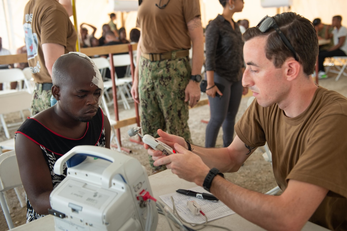 U.S. Navy Hospitalman Adam Lee, assigned to the hospital ship USNS Comfort (T-AH 20), checks the vital signs of a man who has multiple lacerations from a motorcycle accident at a temporary medical treatment site in Port-Au-Prince, Haiti, Nov. 6, 2019.
